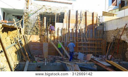 Alora, Spain - July 9, 2019: People Working On Scaffolding On Nw Brown Site Residential Building In