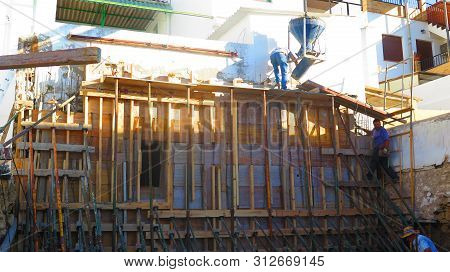 Alora, Spain - July 10, 2019: People Working On Scaffolding On Nw Brown Site Residential Building In