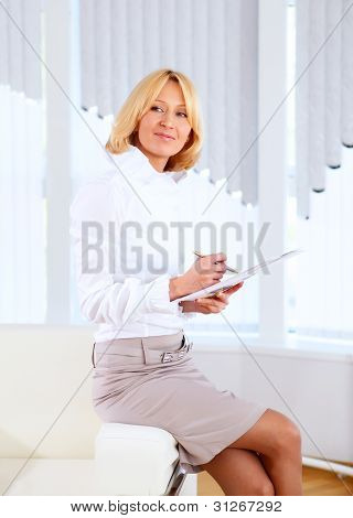 Young beautiful woman in business wear at work