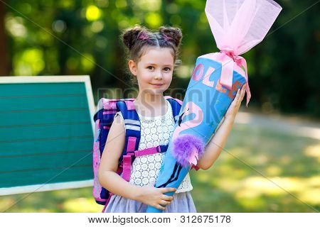 Happy Little Kid Girl By Desk With Backpack Or Satchel And Big School Bag Or Cone Traditional In Ger