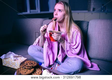 Young Woman Watching Movie At Night. Concentrated Model Eating Ice Cream With Spoon. Sitting On Sofa