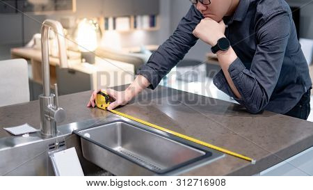 Asian Man Designer Using Tape Measure For Measuring White Granite Countertops On Modern Kitchen Coun