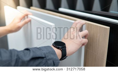 Male Hand Choosing Cabinet Panel Materials Or Countertops For Built-in Furniture Design. Shopping Fu