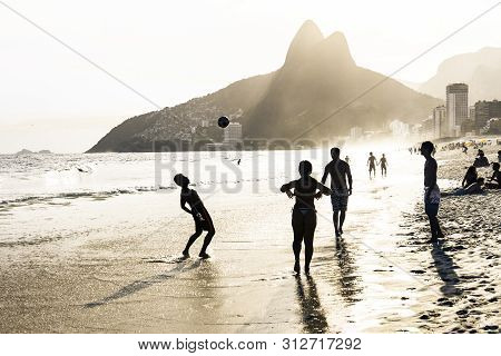 Rio De Janeiro, Brazil - February 24, 2015: A Group Of Brazilians Playing On The Shore Of Ipanema Be