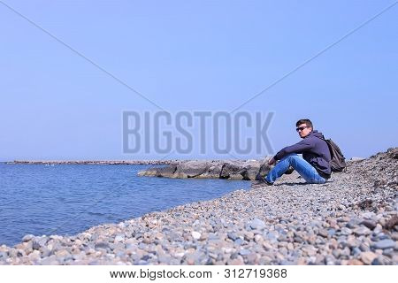 Young Man Traveler Sit On Stone Beach And Looks At Sea Admires Seascape On Spring Vacation, Side Vie