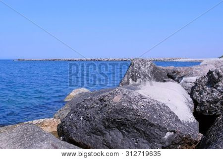 Nature Sea Background With Water, Rocks And Sky. Seascape With Huge Stones, Pier And Blue Water In C