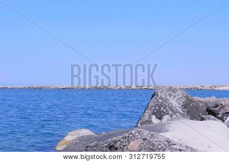 Seascape Background In Bay With Stone Pier. Beautiful Bay On The Sea Coast. Sea Stone Beach In Sunny