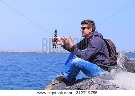 Young Guy Tourist Records Video On Mobile Phone On Sea Background. Travel Blogger Man Shoots Video O
