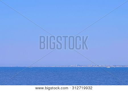 Clear Sunny Summer Day At Sea, View On Coastal Town. Seascape Background With Blue Water, Yachts, Ci