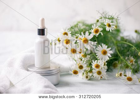 Organic Vegan Natural Cosmetics Concept. Chamomile Flowers And Cosmetic Bottles Of Cream And Serum E