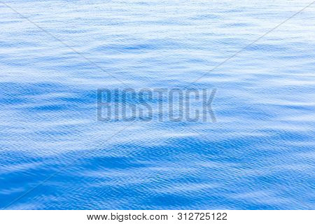 The Background Or Texture Of The Blue Water Surface Of The River, Lake Or Sea With The Waves, Ripple