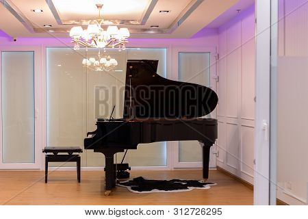 Luxurious Music Room With Grand Piano And Chandelier With Colorful Lighting.