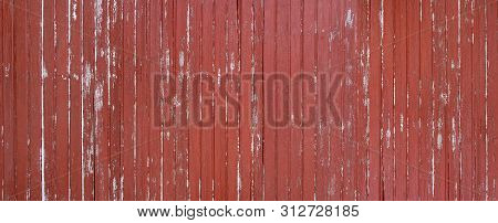 Panorama Of A Weathered Red Brown Wooden Wall Made Of Vertical Boards
