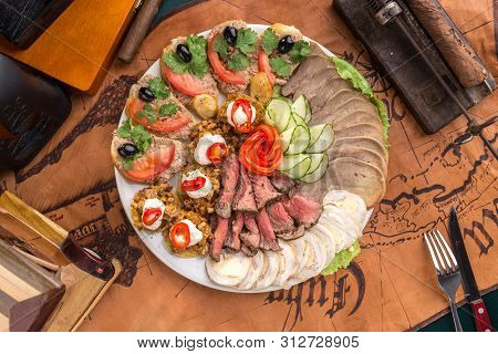 Different Appetizer And Smoked Meat On The Plate On Old Map Background Top View