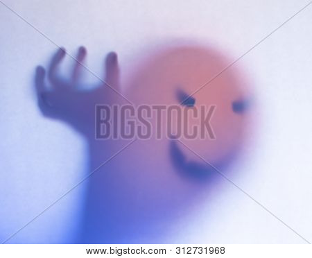 Halloween Blurred Background. A Ghost Resembling A Pumpkin In Color Behind Glass. Terrible And Terri