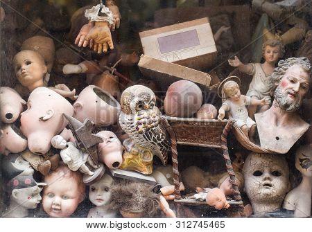 Horizontal Front View Closeup Of Vintage Repair Shop Window With Various Broken Head Puppet Doll Par