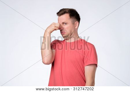 Displeased Young Man Plugs Nose As Smells Something Stink And Unpleasant.