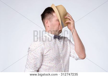 Young Caucasian Man Closes Face With Hat Trying To Stay Anonym.