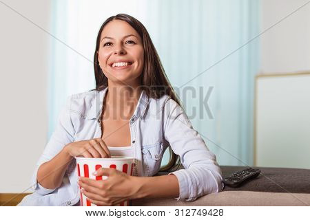 Beautiful Young Smiling Woman Watching A Movie And Eating Popcorn.