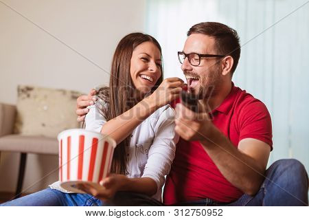 Couple In Love Sitting On A Living Room Sofa, Watching Tv And Eating Popcorn.