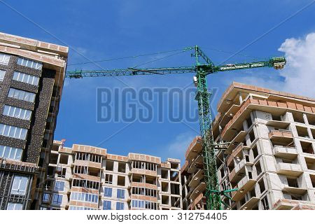 Background Of A Modern Commercial Residential Complex Under Construction. Crane Near The Building Un