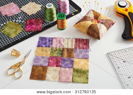 Quilting Block From Bright Square Pieces Of Fabrics, Pincushion, Stacks Of Square Pieces Of Fabrics,