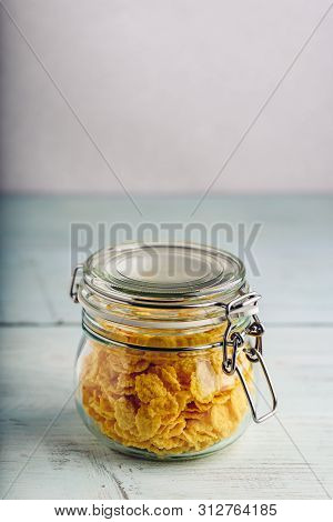 Jar Full Of Corn Flakes On A Wooden Surface
