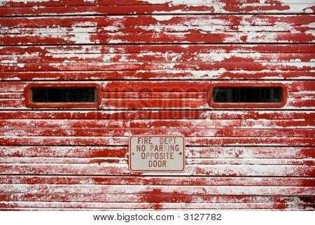 Vintage Fire Department Garage Door With Peeling Red Paint
