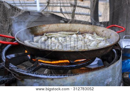 Fried Small Smelt Tasty Fish On A Barbecue Grill Hotplate. Lot Of Tasty Delicious Fried Fish Of Smel