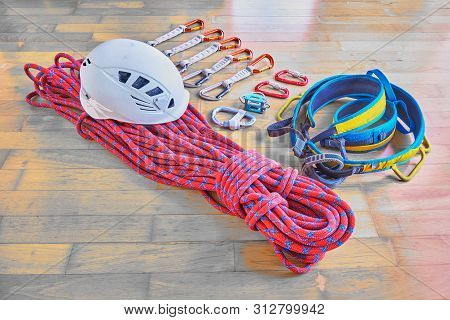 Climbing Equipment On Wooden Background: Red Dynamic Rope With Blue Stripes, Helmet, Blue/yellow Har