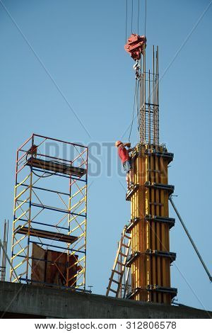 A Construction Worker Controls The Crane Movement When Assembling Building Blocks Against A Blue Sky