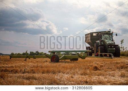 A Tractor For Collecting Wheat From A Combine Harvester Stands On A Field Of Mown Wheat Against A Bl