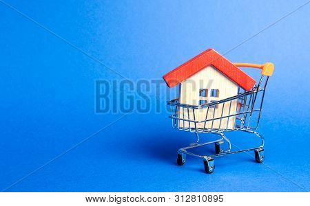 Wooden House In A Supermarket Trading Cart. The Concept Of Buying A House Or Apartment. Affordable H