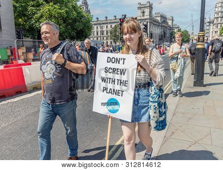 London / Uk - June 26th 2019 - Young Woman Carries A Climate Change Sign Outside Parliament, As Part