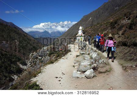 Sagarmatha national park, Nepal - May 17, 2019: Group of tourists hike in Himalayas mountains on Everest trek near Pangboche, Sagarmatha national park, Solukhumbu, Nepal
