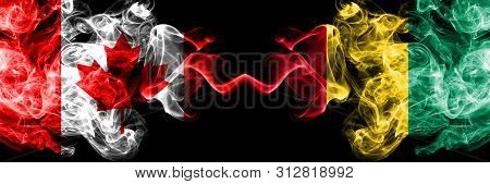 Canada Vs Guinea, Guinean Smoky Mystic Flags Placed Side By Side. Thick Colored Silky Smoke Flags Of