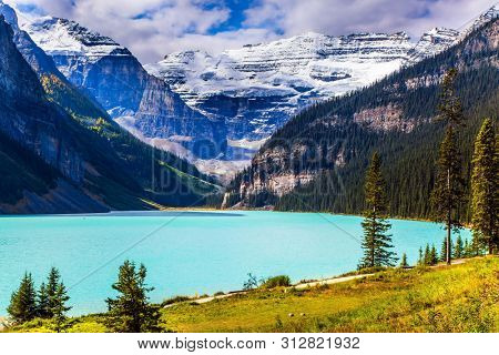 Travel to the Rocky Mountains of Canada. The lake with azure water is surrounded by mountains and forests. Glacial Lake Louise. Sunny fine day. The concept of ecological, active and photo tourism