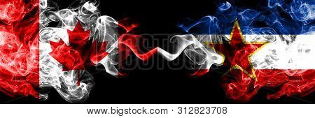 Canada Vs Yugoslavia Smoky Mystic Flags Placed Side By Side. Thick Colored Silky Smoke Flags Of Cana