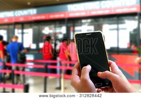 Hand Using Smartphone At Bus Terminal Ticketing Counters