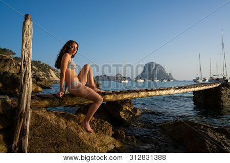 Ibiza cala d Hort girl on pier sunset Es Vedra islet Balearic Islands