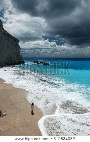 Young beautiful woman looks at the sea on the Porto Katsiki beach, Lefkada island, Greece.