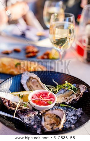 Fresh oysters served in a restaurant with white wine