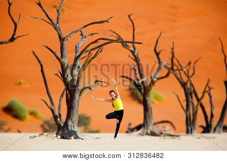 Adorable young girl among dead camelthorn trees surrounded by red dunes in Deadvlei in Namibia