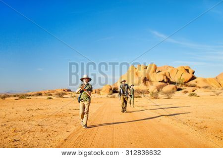 Family father and two kids hiking in Spitzkoppe area with unique rock formations in Damaraland Namibia