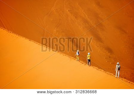 Family of mother and two kids climbing up famous red sand dune Big Daddy in Sossusvlei Namibia