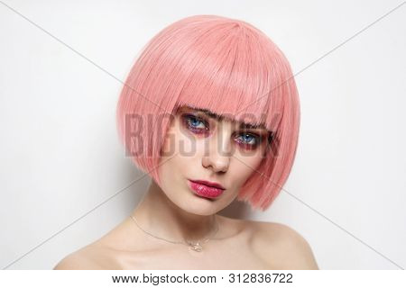 Vintage style portrait of young beautiful woman with pink hair and fancy glitter makeup