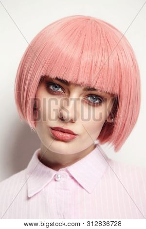 Vintage style portrait of young beautiful woman in fancy pink wig