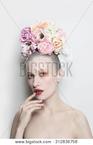 Vintage style portrait of young beautiful girl with fancy flower hairdo