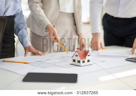 architecture, construction business and people concept - close up of architects discussing blueprint of house project at office