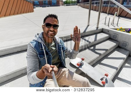 leisure, people and lifestyle concept - smiling indian man in sunglasses waving hand and taking picture by selfie stick on roof top